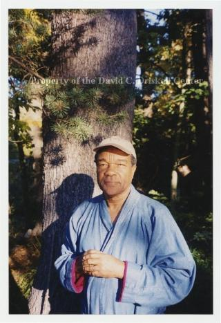 David C. Driskell standing in front of tree wearing baseball cap