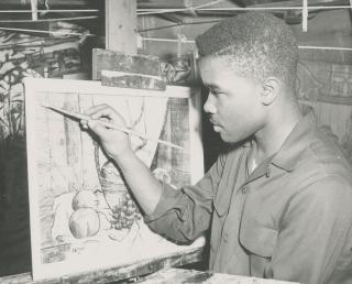 Young David C. Driskell in black and white painting a still life