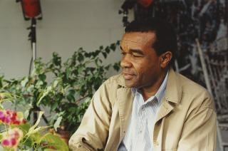 David C. Driskell in color surrounded by plants looking off to his right